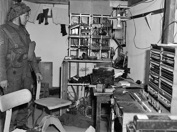 Corporal W. Nichorster, Royal Canadian Corps of Signals, in the underground switchboard of a captured German radar station near Beny-sur-Mer, France, 17 June 1944.