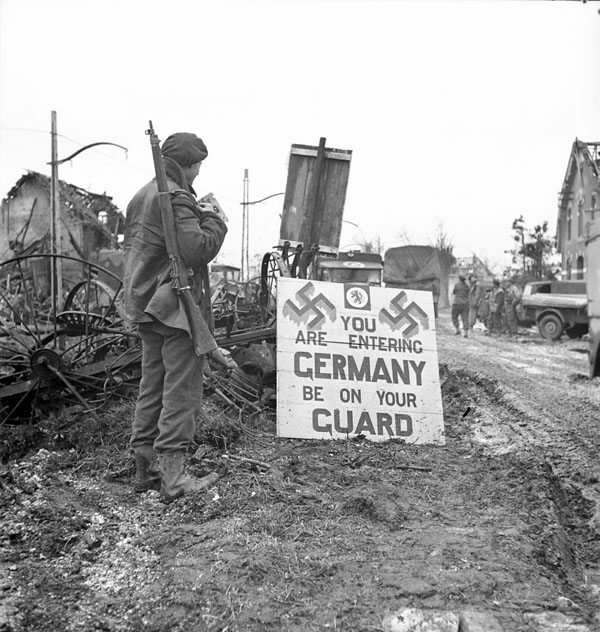 Corporal Urban Mayo, 13th Field Company, Royal Canadian Engineers (R.C.E.), with a sign that reads