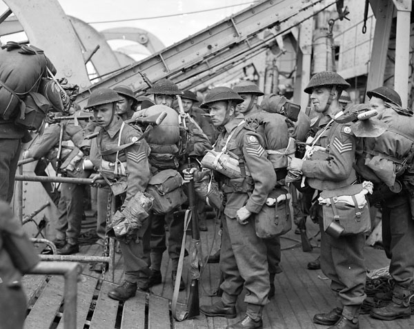 Three sergeants of the Royal Berkshire Regiment (British Army) disembarking from H.M.C.S. PRINCE DAVID on D-Day, France, 6 June 1944.