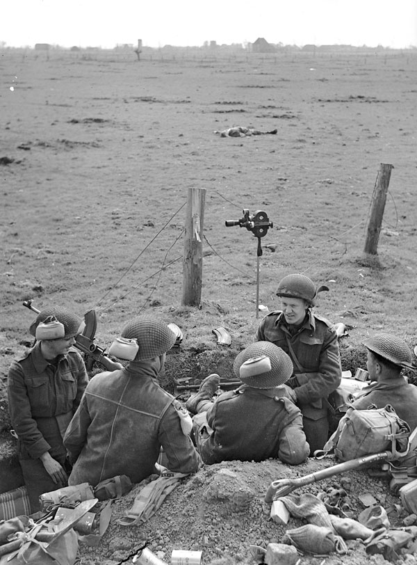 Sergeant F. Beal (fourth from left), Canadian Army Film and Photo Unit, talking with infantrymen of the Royal Hamilton Light Infantry (R.H.L.I.), Speldrop, Germany, 24 March 1945.