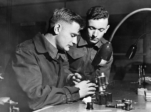 Personnel of Base Workshop, Royal Canadian Electrical and Mechanical Engineers (R.C.E.M.E.), repairing captured German binoculars, Bordon, England, 6 January 1945.