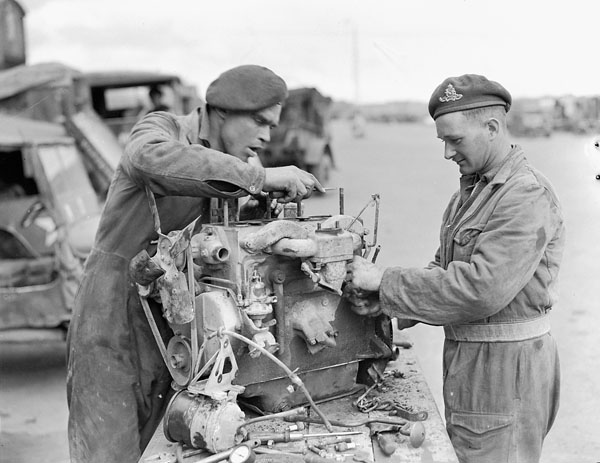 Gunners S.S. Lott and J.G. Spear, 17th Field Regiment, Royal Canadian Artillery (R.C.A.), overhauling a jeep motor, 11th Infantry Brigade, Royal Canadian Electrical and Mechanical Engineers (R.C.E.M.E.), Groningen, Netherlands, 28 April 1945.