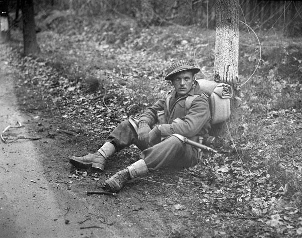 Private N.J. Ingram, Perth Regiment, stops for a rest north of Arnhem, Netherlands, 15 April 1945.