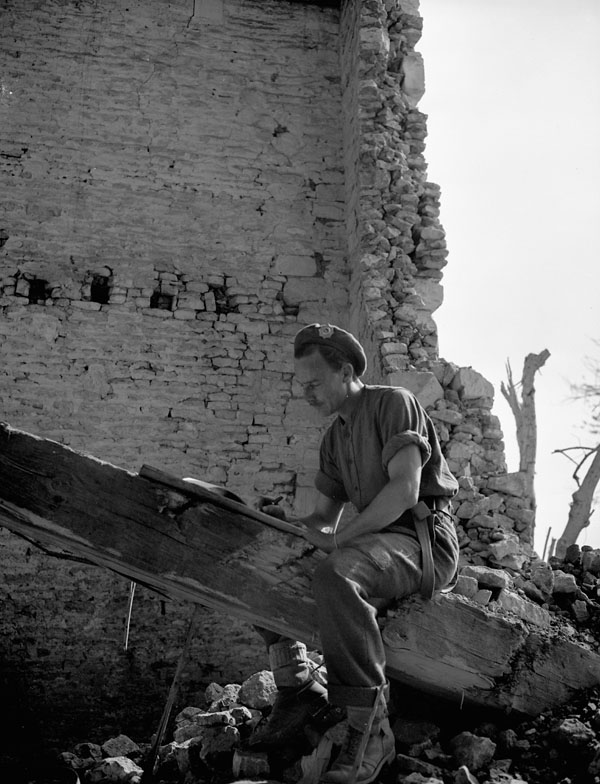 Corporal W. Salmond of the South Saskatchewan Regiment writing a letter home in the ruins of a building at Rocquancourt, France, 11 August 1944.