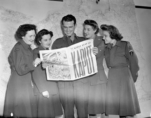 A group at SHAEF Headquarters reading the special VE-Day edition of the MAPLE LEAF newspaper, Paris, France, 11 May 1945.