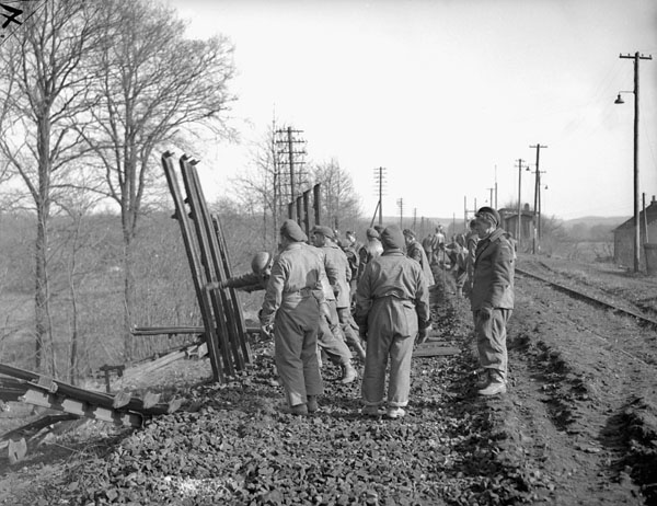 Personnel of the 9th Field Squadron, Royal Canadian Engineers (R.C.E.), lifting rails to make a road for Canadian vehicles near the Hochwald, Germany, 2 March 1945.