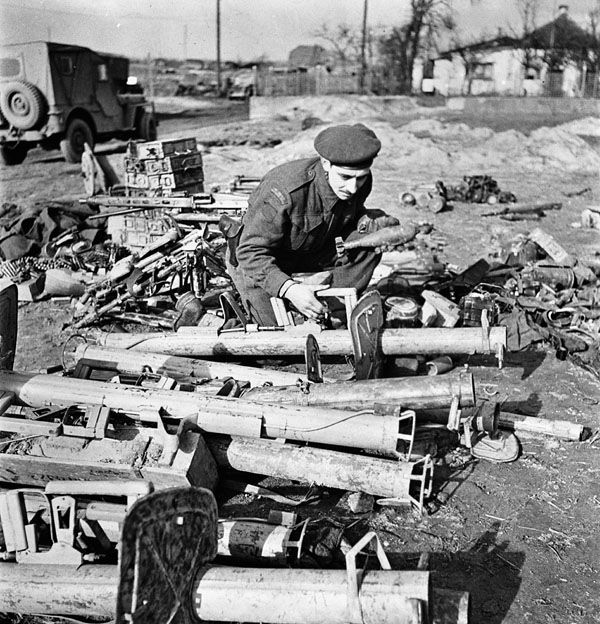 Private R. Langlois of the 2nd Canadian Infantry Division examining a collection of captured German weapons, which include a Panzerfaust anti-tank weapon, near the Hochwald, Germany, 3 March 1945.