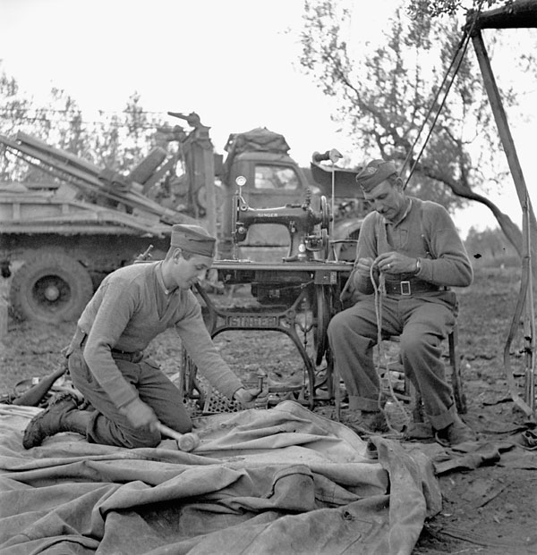 Private W.A. Lloyd repairs a tarpaulin while Lance-Corporal W.L. Milburn mends rope, 1st Infantry Brigade Workshop, Royal Canadian Electrical and Mechanical Engineers (R.C.E.M.E.), San Leonardo di Ortona, Italy, 13 December 1943.