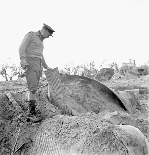 Lieutenant C. Allen standing at the entrance to a  collapsed German network of underground tunnels beneath a site now occupied by the Sub-Park, Royal Canadian Ordnance Corps, 1st Canadian Army Tank Brigade, San Leonardo di Ortona, Italy, 13 December 1943.