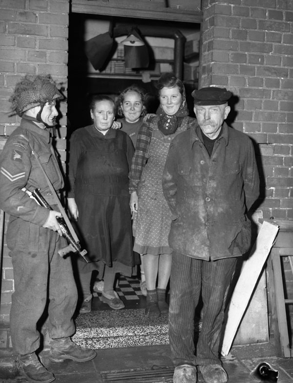 Corporal Lewis G. Wiseman (left), 1st Canadian Parachute Battalion, talking with a store owner and his family, Lermbeck, Germany, 29 March 1945.