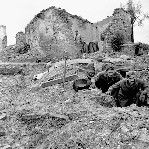 Sergeant F.V. MacDougal and Sergeant-Major J.H. Ferguson, 2nd Field Regiment, Royal Canadian Artillery (R.C.A.), emerging from their dugout north of Ortona, Italy, 15 February 1944.