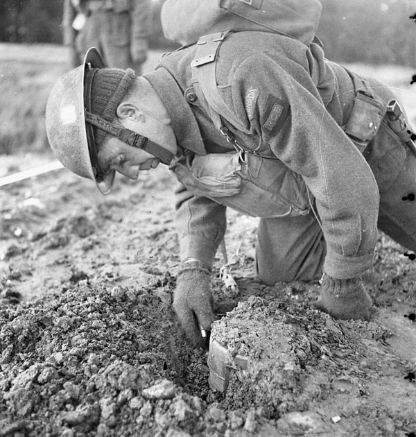 An unidentified member of the 9th Field Squadron, Royal Canadian Engineers (R.C.E.), taking part in the demonstration of a Polish mine detector, England, 30 January 1943.