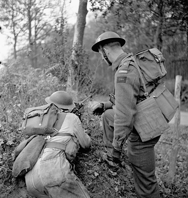 Unidentified infantrymen of the Cape Breton Highlanders, one of whom is armed with a Boys anti-tank rifle, taking part in a training exercise, England, 24 November 1942.