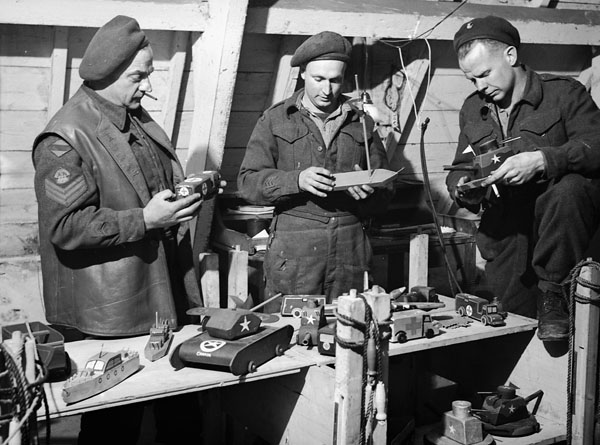 Personnel of No. 2 Motor Ambulance Convoy Detachment, Royal Canadian Army Service Corps (R.C.A.S.C.), displaying toys which will be presented to Dutch children during a Christmas party, Nijmegen, Netherlands, 20 December 1944.