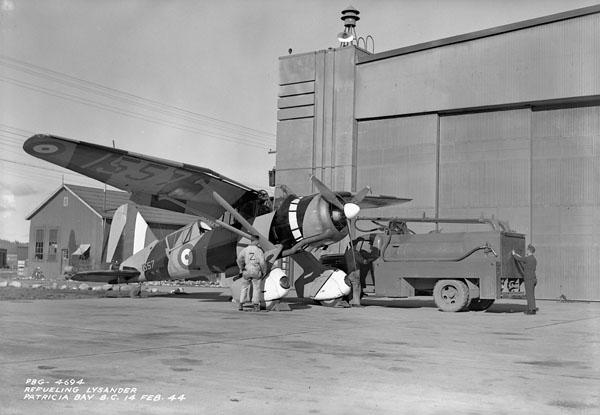 Groundcrew refuelling Westland Lysander IIT target tug aircraft 1557 of No.3 Operational Training Unit (Royal Canadian Airforce Schools and Training Units), Royal Canadian Air Force (R.C.A.F.), Patricia Bay, British Columbia, Canada, 14 February 1944.