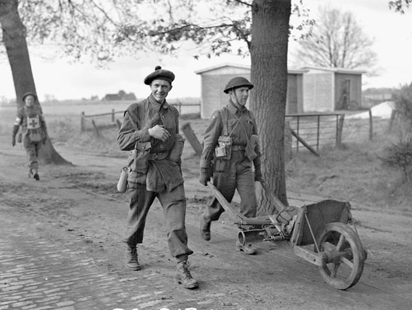 Infantrymen of the Queen's Own Cameron Highlanders of Canada hauling surplus kit in a wheelbarrow near Oldenburg, Germany.