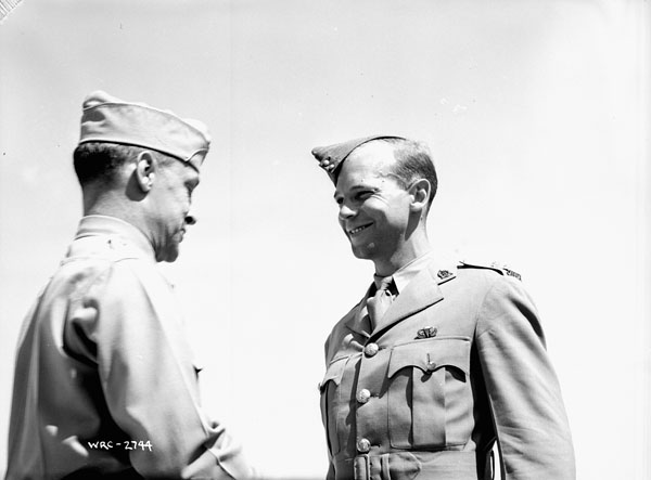 "Colonel G.P. Howell (left), Commandant, U.S. Army Parachute School, presenting American  ""Jump Wings"" to Captain C.F. Hyndman, Medical Officer, 1st Canadian Parachute Battalion, Fort Benning, Georgia, United States, 12 September 1942."