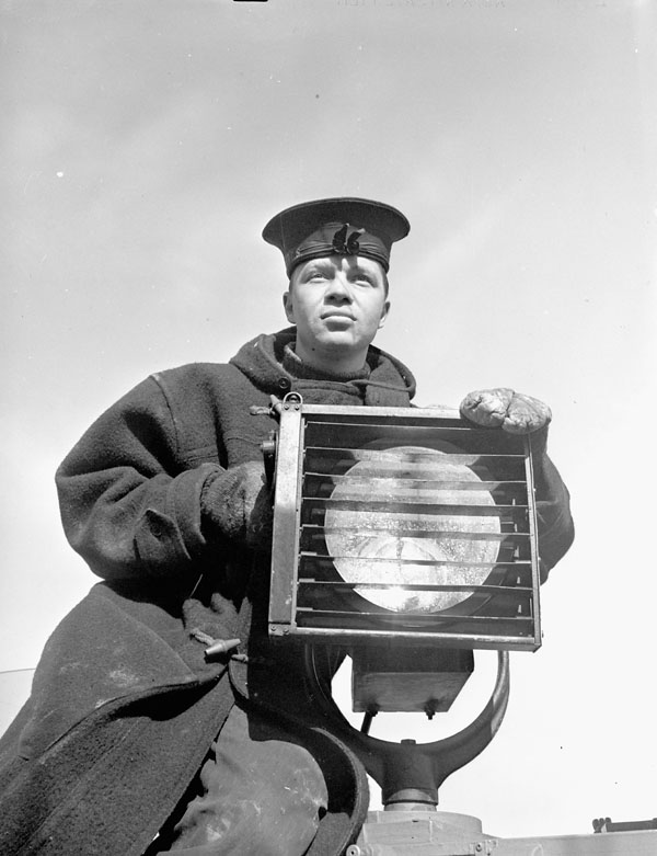 An unidentified signalman aboard the Fairmile motor launch Q078 of the Royal Canadian Navy (R.C.N.) at sea, 10 May 1943.