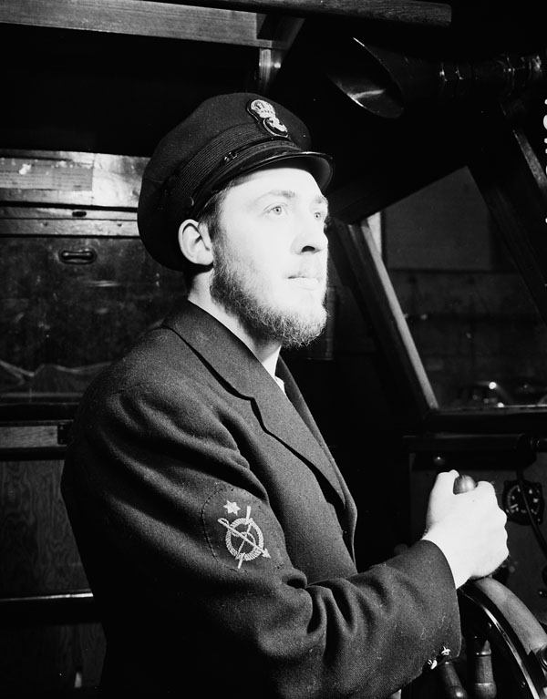 An unidentified petty officer at the wheel of the Fairmile motor launch Q078 of the Royal Canadian Navy (R.C.N.) at sea, 10 May 1943.