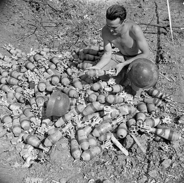 Private J.O. Hayman examining a heap of Italian-made mortar bombs abandoned by a German Panzer Grenadier unit near Aquino, Italy, 22 May 1944.