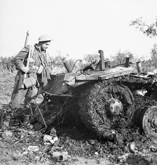 Private G.C. Butcher, 48th Highlanders of Canada, examines the wreckage of a German PzKpfW III tank destroyed by the Calgary Regiment, San Leonardo di Ortona, Italy, 10 December 1943.