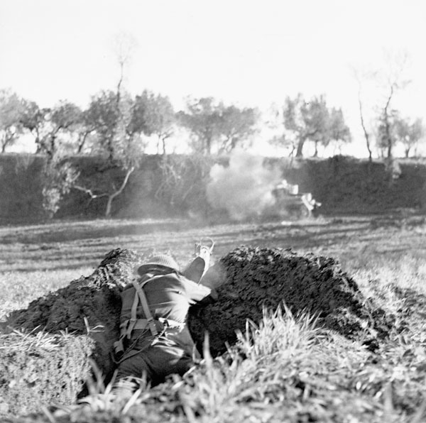 An unidentified member of the West Nova Scotia Regiment firing a PIAT anti-tank weapon at the 3rd Canadian Infantry Brigade's training school west of Ortona, Italy, 10 January 1944.