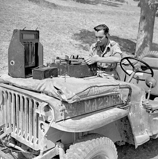 Engineer Paul Johnston  of the Canadian Broadcasting Corporation setting up equipment to record a broadcast by CBC correspondent Matthew Halton, Catangora, Italy, 14 September 1943.