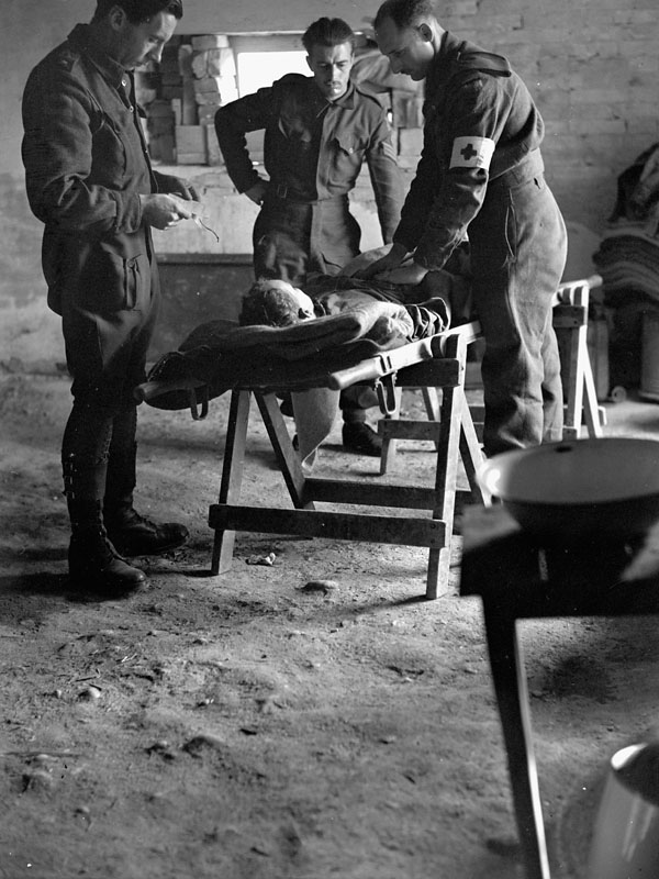 Personnel of the Royal Canadian Army Medical Corps checking the condition of a wounded Canadian soldier being evacuated to a Field Surgical Unit.
