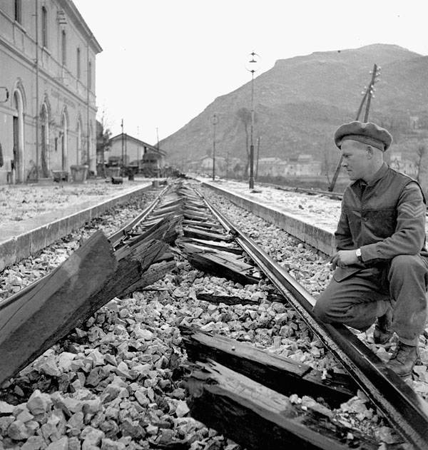 Sergeant F.H.J. Ricketts examining railway ties which were cut by the last German train through Carovilli, Italy, 26 November 1943.