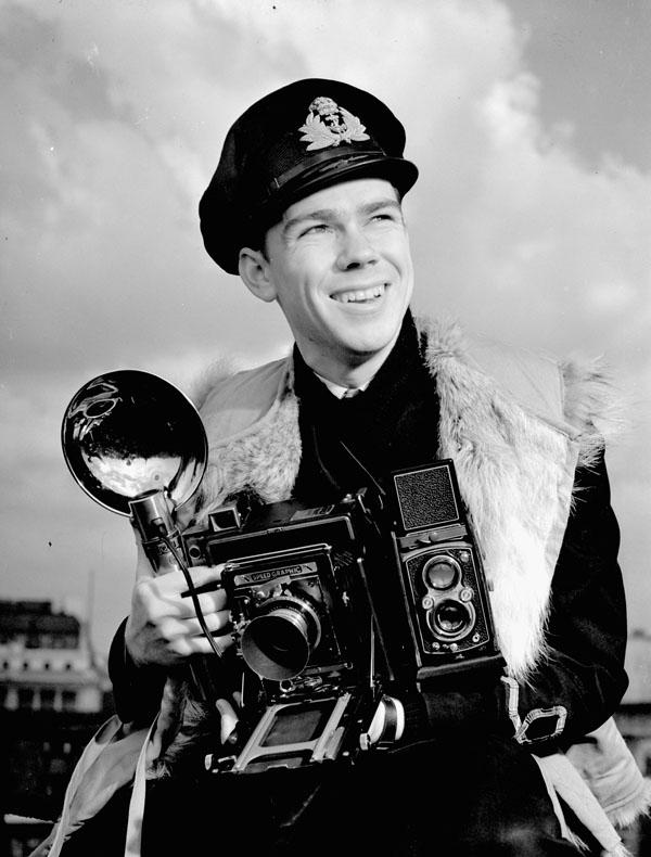 Lieutenant John D. Mahoney of the Royal Canadian Navy Volunteer Reserve, holding an Anniversary Speed Graphic camera.