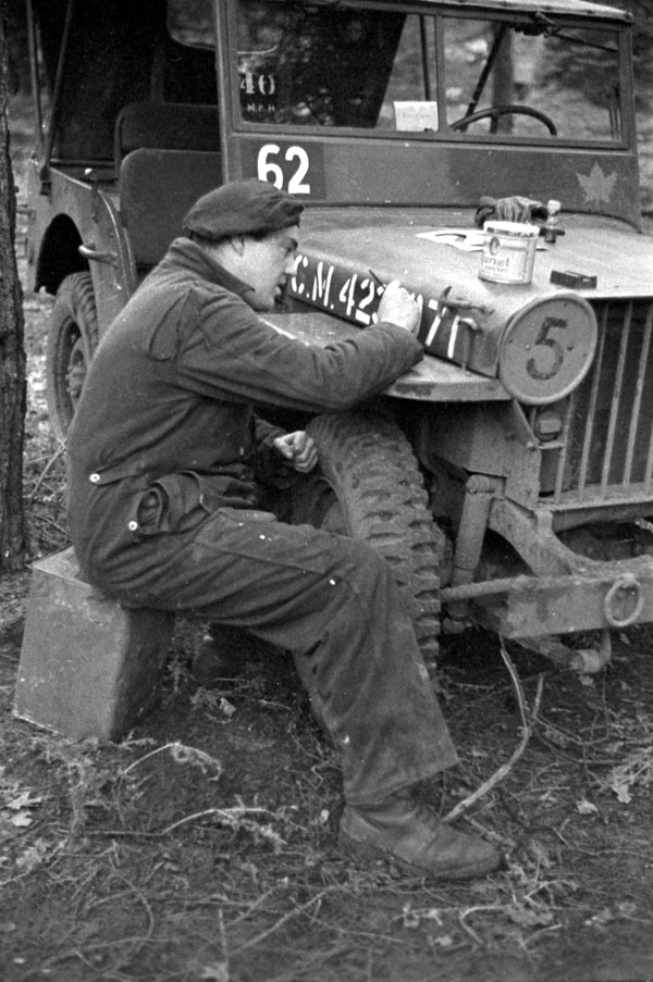 Unidentified soldier stencilling numbers on the hood of a jeep, England, 21 December 1943.