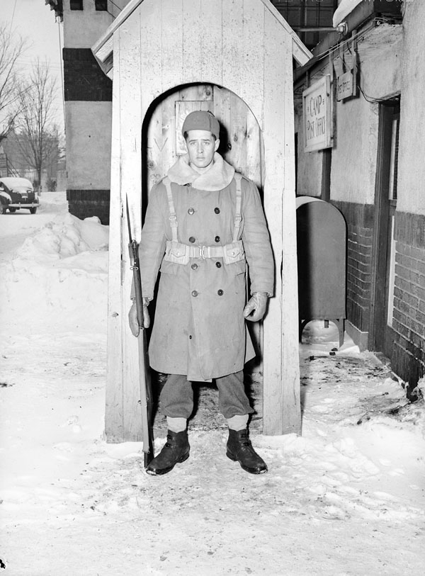 An unidentified sentry, who wears a winter overcoat and webbing, at Lansdowne Park, Ottawa, Ontario, Canada, February 1942.