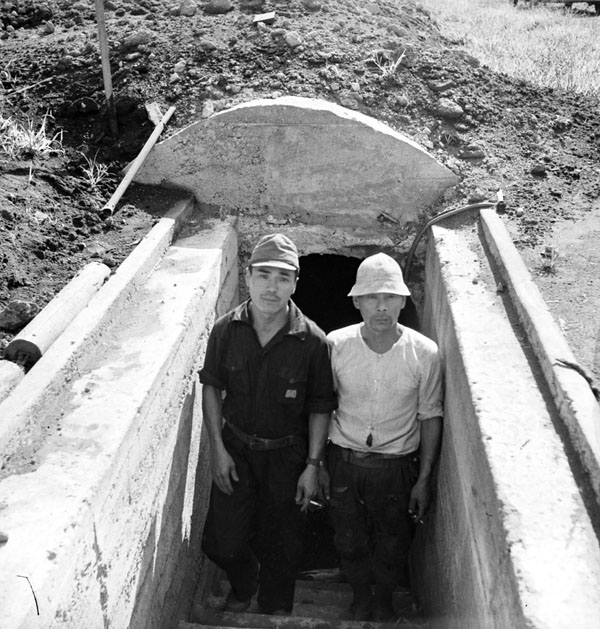 Two Japanese soldiers emerging from an air-raid shelter, Atsugi, Japan, 1945.