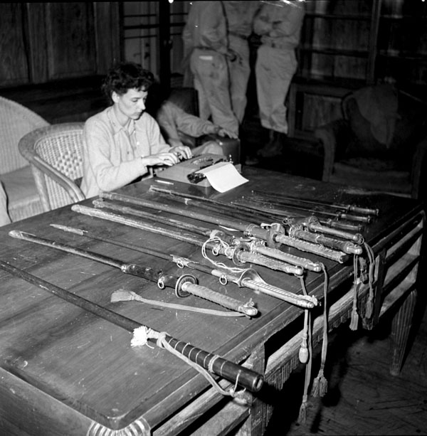 War correspondent Shelley Mydans of Life magazine typing an article while sitting beside a display of swords surrendered by Japanese officers, Japan, August 1945.