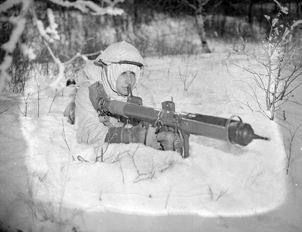 An unidentified parachute-qualified soldier, who is armed with a PIAT anti-tank weapon, undertaking winter infantry training at A-35 Canadian Parachute Training Centre (Canadian Army Training Centres and Schools), Camp Shilo, Manitoba, Canada, 20 March 1945.