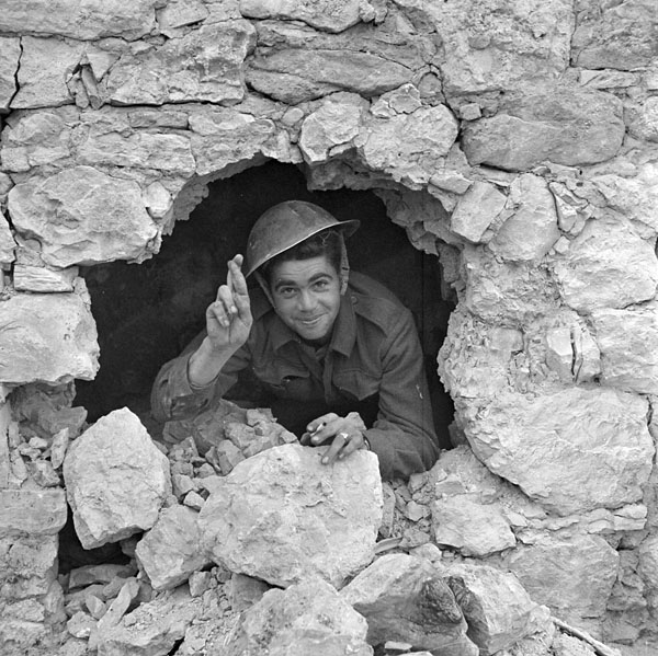 Private J.A. Robb of The Loyal Edmonton Regiment looking through a shell hole in the foundation of a building, Colle d'Anchise, Italy, 27 October 1943.