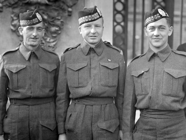 Private Leonard A. Middleton (centre) of The Toronto Scottish Regiment, who received the Military Medal during an investiture at Buckingham Palace, London, England, 27 October 1942.