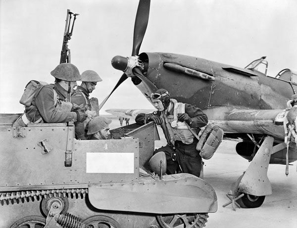 Infantrymen of The Lincoln and Welland Regiment, who are riding in a Universal Carrier, talking with F/O O.K. Morgan, who stands in front of a Hawker Hurricane XII aircraft of No.127(F) Squadron, R.C.A.F., Gander, Newfoundland, May 1943.