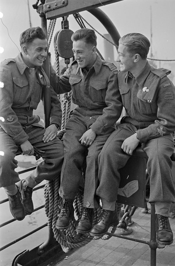 Three unidentified infantrymen of Les Fusiliers Mont-Royal waiting to disembark from a troopship at No.7 Pier, Glasgow, Scotland, 16 April 1942.