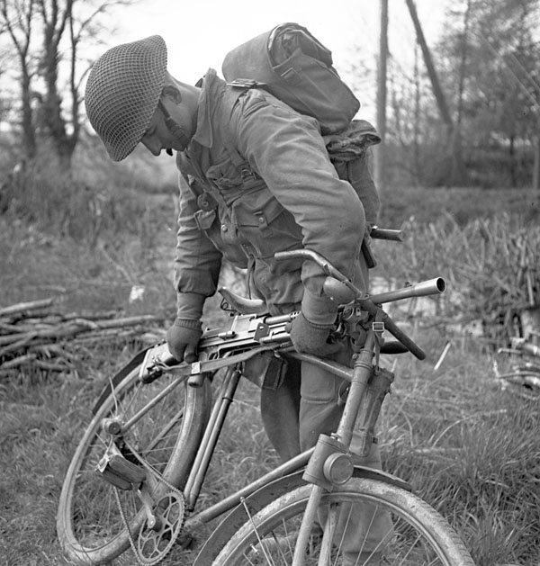 An unidentified Bren gunner, who is securing his gun on a special weapons rack on his bicycle, taking part in a 1st Canadian Infantry Division training exercise, England, ca. 1-3 April 1943.