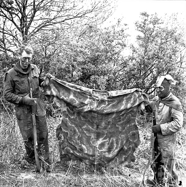 Unidentified infantrymen of the 2nd Canadian Infantry Division, who are taking a sniping - stalking-camouflage training course, displaying a camouflaged poncho used to provide additional cover. England, 23 April 1943.