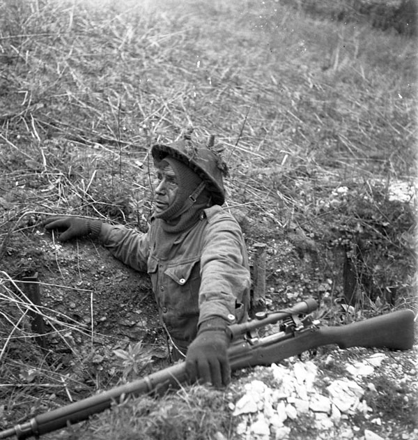 An unidentified infantryman of the 2nd Canadian Infantry Division, who is armed with a sniper rifle and scope, taking part in a sniping-stalking-camouflage training course, England, 23 April 1943.