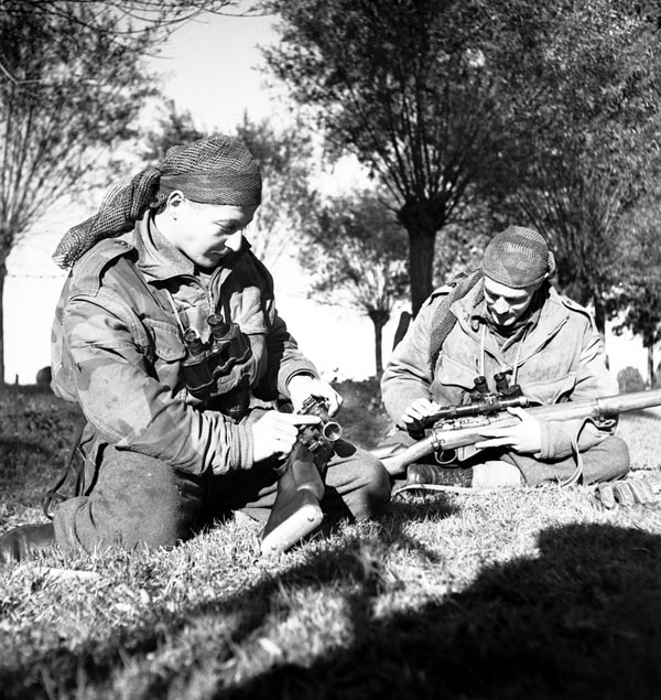 Corporal S. Kormendy and Sergeant H.A. Marshall of The Calgary Highlanders cleaning the telescopic sights of their No.4 MkI(T) rifles during a scouting, stalking and sniping course, Kapellen, Belgium, 6 October 1944.