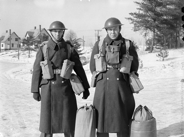 Unidentified Canadian soldiers, who are wearing greatcoats, web equipment, and steel helmets, Petawawa, Ontario, Canada, 1943.