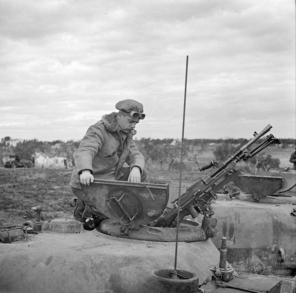An unidentified crew commander of the 8th Princess Louise's (New Brunswick) Hussars looking into his Sherman tank's access hatch during a predicted tank shoot, Italy, 2 March 1944.