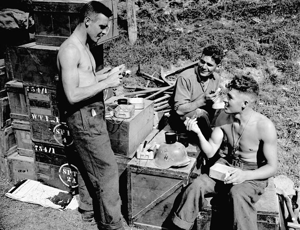 Privates H.A. Fraser, G.R. Wood and W.F. Sager, all of the Highland Light Infantry of Canada, eating lunch on a makeshift table, on which can be seen a German Waffen SS helmet, Thaon, France, 6 August 1944.