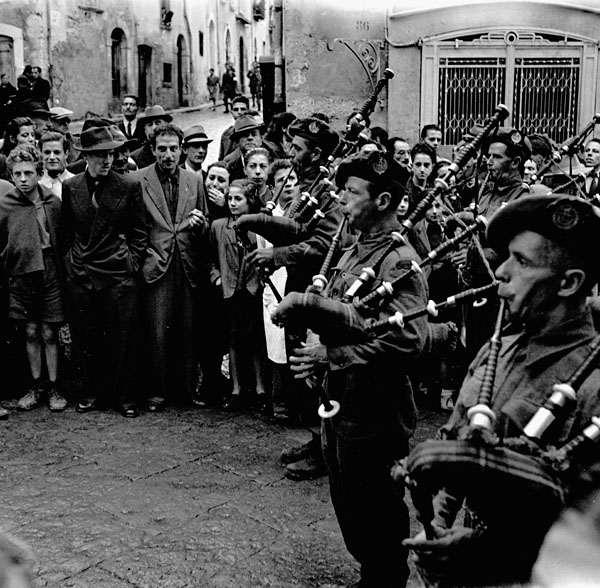 Pipers, possibly of the 48th Highlanders of Canada, playing in the streets of Campobasso, Italy, 18 October 1943.