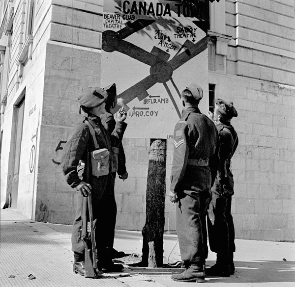 "Canadian soldiers looking at the ""Canada Town"" billboard, Campobasso, Italy, 21 October 1943."
