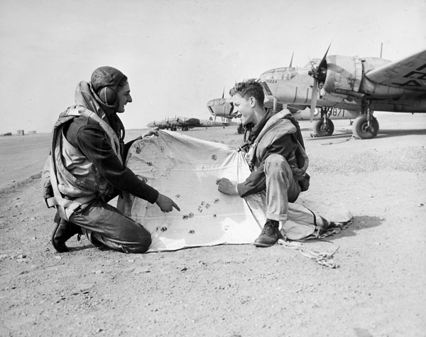 Counting the hits: two unidentified aircrew examining a target drogue at No. 10 Bombing and Gunnery School, RCAF.