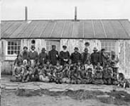 MIKAN 3194505 Reverend Edmund Peck and a group of Inuit, Blacklead Island, Cumberland Sound. [The man standing to the left of Reverend Peck is Peter Tulugarjuaq. The man in the back row on the far right is Nattiapik, ancestor of the Kilabuk family]  [September 5, 1903]. [Reverend Edmund Peck and a group of Inuit, Blacklead Island, Cumberland Sound. [The man standing to the left of Reverend Peck is Peter Tulugarjuaq. The man in the back row on the far right is Nattiapik, ancestor of the Kilabuk family], [September 5, 1903].]